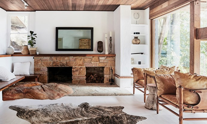 The downstairs living room is swathed in raw materials. A sandstone fireplace and large rock, which protrudes through the floor, are standout features.