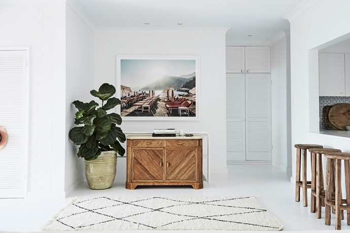 "The hallway next to the kitchen has been thoughtfully styled with an antique bamboo and marble sideboard, thriving [fiddle leaf fig plant](https://www.homestolove.com.au/tips-for-caring-for-fiddle-leaf-fig-trees-4923|target=""_blank""), beni ourain rug and an eye-catching art print by Olivia's friend, Stuart Cantor."