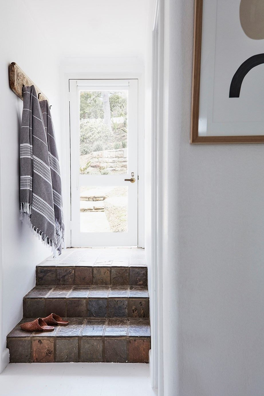 This narrow entryway would be impractical and uninviting without the simple addition of some vintage hooks to hang towels, school bags or hats.