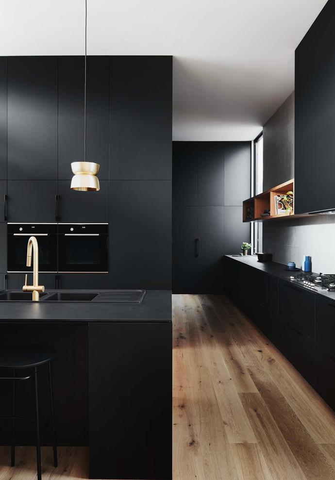 Striking black cabinetry and gleaming brass create a cosmic kitchen with universal appeal courtesy of Auhaus Architecture. *Photograph*: Mike Baker | *Styling*: Heather Nette King.