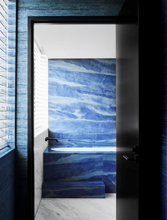 Slabs of azure marble and crisp white elements ripple in a frothy marine milieu in this bathroom designed by Poco Designs.