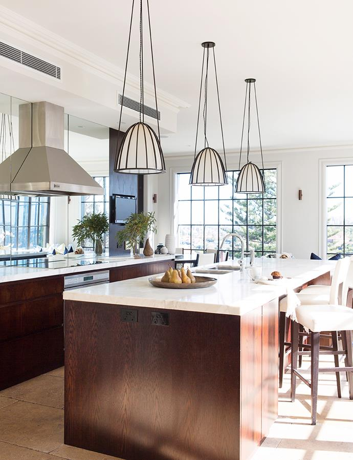 A hint toward the Art Deco period, these intricate pendant lamps not only help to create intimate lighting but serve as a talking point in this entertainer's kitchen. *Image: Simon Whitbread / bauersyndication.com.au*