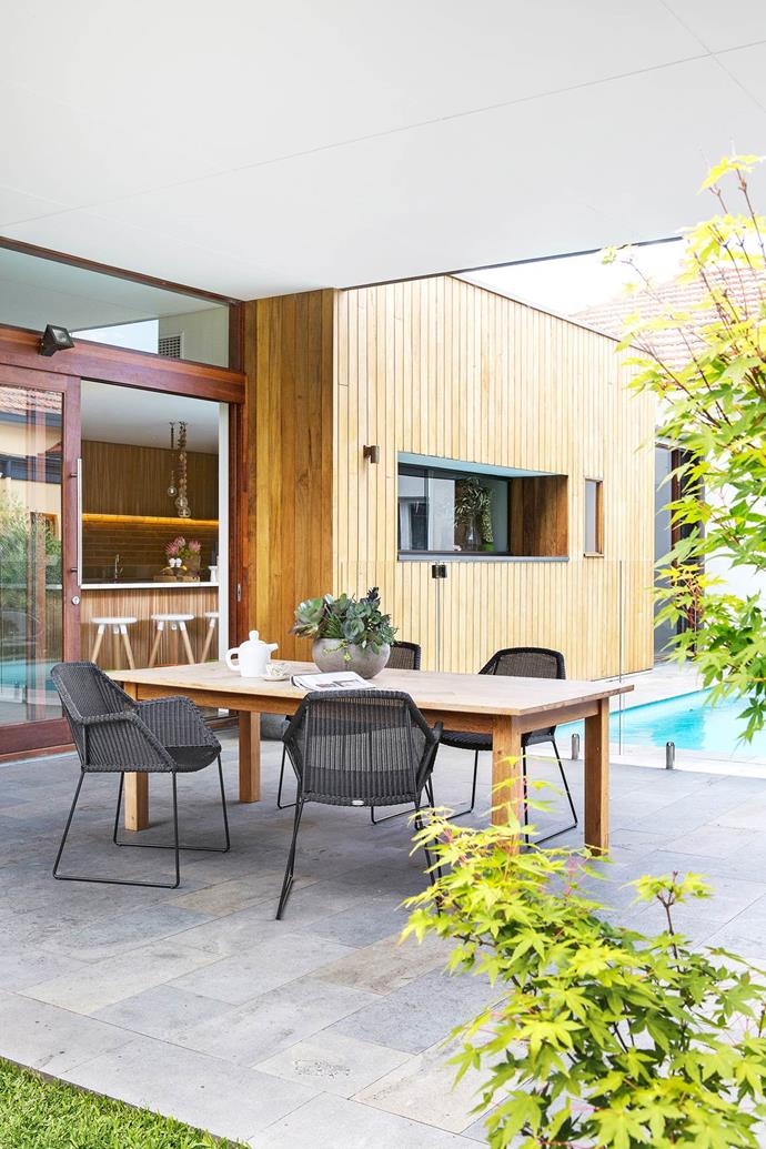 "The outdoor dining area is nestled between the pool and the expanse of lawn of [this 1930s bungalow](https://www.homestolove.com.au/1930s-bungalow-gets-a-retro-style-revamp-2951|target=""_blank""). Caneline outdoor dining chairs, DesignFarm. Doors and windows by Cockburn Joinery (throughout). Exterior cladding is Trendplank in Pacific Teak, Mortlock Timber. Bluestone pavers, Eco Outdoor. *Photograph*: Angelita Bonetti"