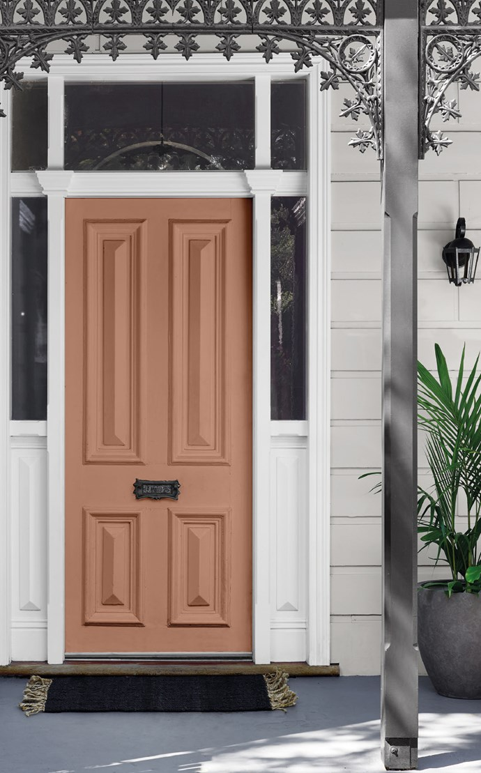 """For an on-trend look, Andrea suggests apricot or terracotta coloured accents on the door and verandah accessories against a predominantly white exterior with black or charcoal trims. """"At dusk, the soft sunlight can create a metallic-like effect with some tan and apricot tones, which can add another layer of depth and dimension to the scheme."""" Here the front door is painted in Dulux 'Very Terracotta""""."""