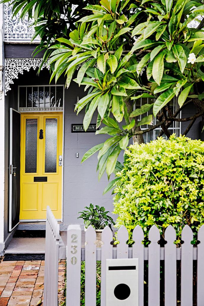 A yellow front door and a frangipani tree create a warm (and fragrant) entrance to this refreshed terrace. *Photo:* James Henry / *bauersyndcation.com.au*
