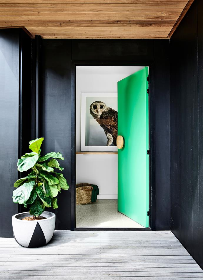 "Talk about making an entrance! A dramatic charcoal exterior is livened up by a bright green front door and a [fiddle leaf fig tree](https://www.homestolove.com.au/tips-for-caring-for-fiddle-leaf-fig-trees-4923|target=""_blank""), while a showstopping photographic print keeps the wow-factor going as you enter this Mornington Peninsula home. *Photo:* Derek Swalwell / *Australian House & Garden*"