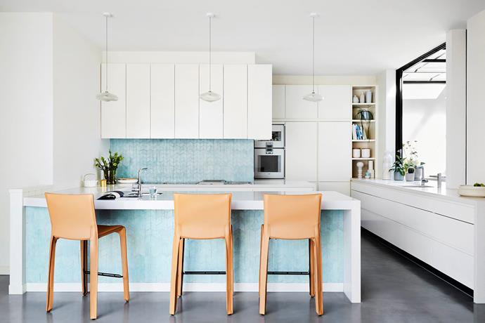 Renovated by the previous owners, the predominantly white kitchen with hidden butler's pantry is livened up with turquoise tiles from Perini lining the splashback and island. Cab leather stools by Cassina are stylish and practical.