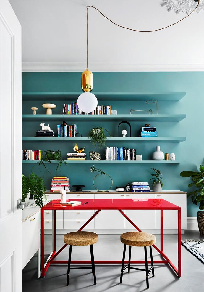 In the home office, a shot of watermelon comes courtesy of the Strut table from Blu Dot. Above it hangs Parachilna lighting and below it sit Sinnerlig stools from Ikea. Open shelves allow the homeowners to display their favourite items and collectibles.