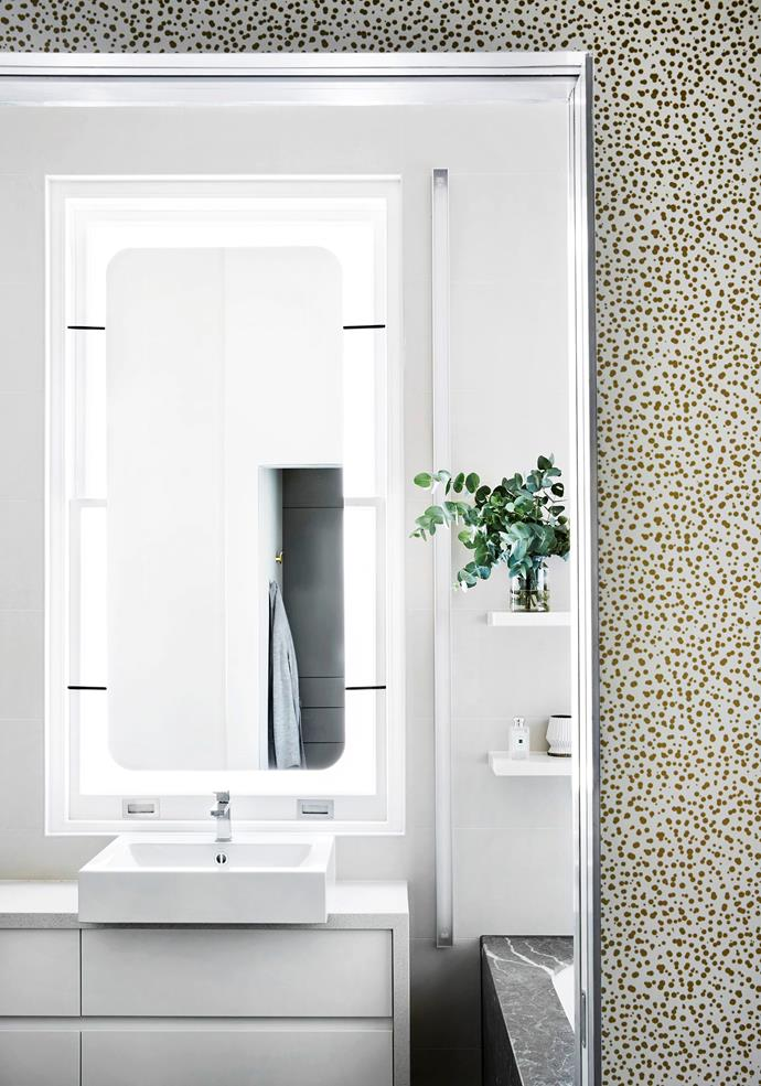 The walk-in wardrobe is wallpapered in a gold-dot pattern from Porter's Paints and leads to the master ensuite. It has a mirror that floats over the window, allowing natural light to bounce around.