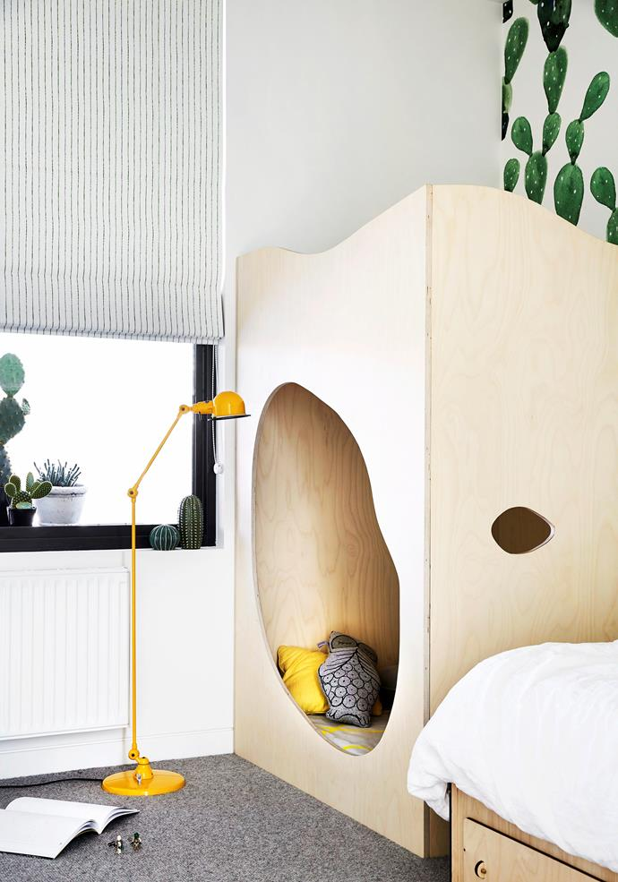 """The wallpaper is perfect for this little boy's room as he loves cactuses."" A Plyroom bed shares floorspace with a custom-made plywood cubby nook. ""We designed this capsule,"" Lauren says. ""It's full of cushions and books and is a great hiding spot."" The bright yellow floorlamp is from Jieldé."