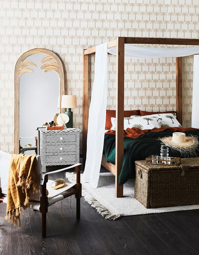 "Aren canopy bed, $3850 for queen, InArtisan. Mallorca trunk, $149, Freedom. Campaign safari chair in Black Fumed Oak with White Cotton Canvas, $628, Dunlin. Gabriella mirror, $1195, Sarah Ellison. **ON BED:** Cassian linen blend fabric, $24.99 per m, Spotlight. 100% linen flat sheet in Tobacco, $180 for queen, 100% linen standard pillowslips in Tobacco, $85 for set of 2, and Washed cotton duvet cover in Forest, $185 for queen, In Bed. Les Palmiers pillows in Classic Palm, $99 for pair, Kawaiian Lion. **ON WALL:** Barneby Gates ""Marrakech Palms"" wallpaper in Gold on White, $180 for 10m roll, Wallpaper Trader."