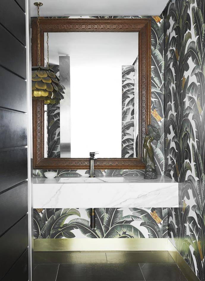 The powder room echoes the tropical plantings with its leaf-motif wallpaper.