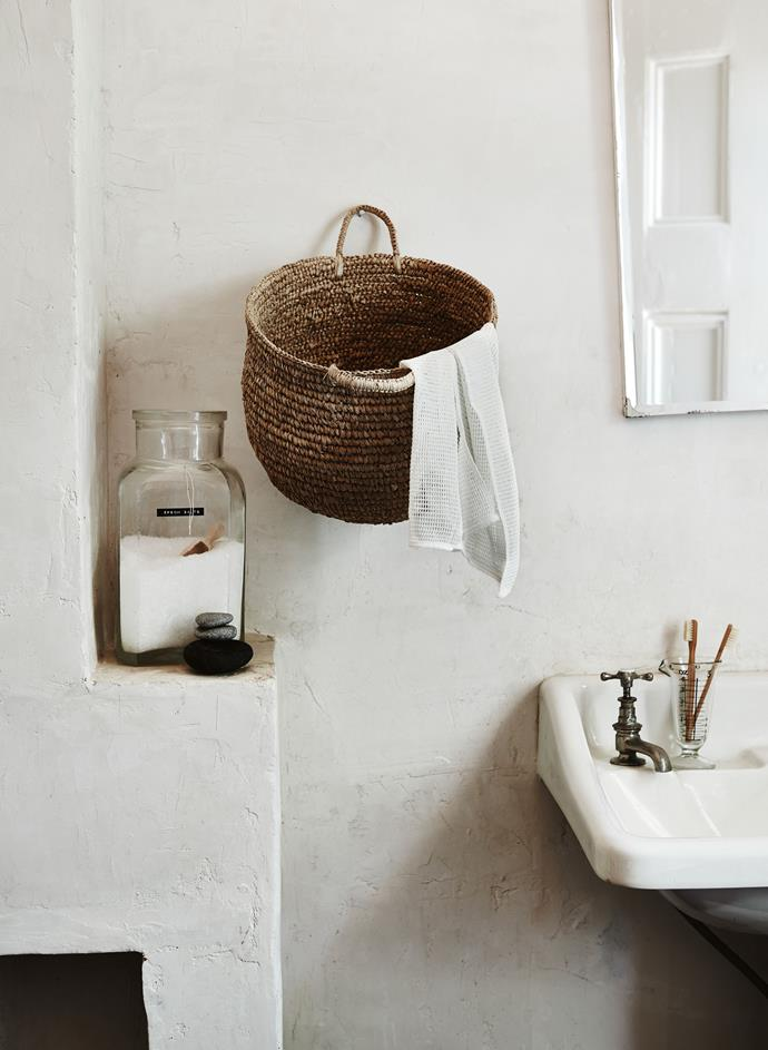**Go vertical**: If you've got a pedestal sink and a bathroom mirror that isn't equipped with a cabinet, it can pay to get creative and go vertical with your storage. In this bathroom, a wicker basket has been nailed to the wall for a handy place to drape a hand towel while also providing ample storage to help keep the sink top free from clutter.