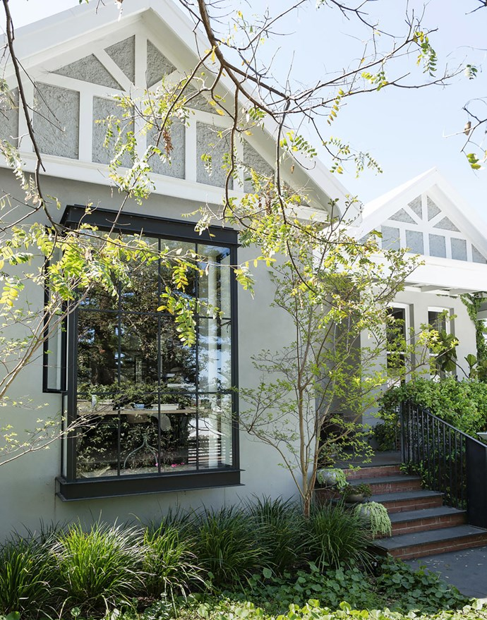 """""""Having been disfigured by many previous owners – one of whom bricked up the front window – we wanted to restore the home's 1911 facade as best we could."""" Crepe myrtles are planted on either side of the steel-framed bay window."""