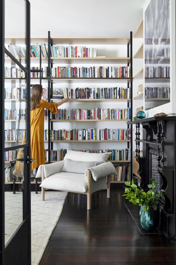 """""""My lifelong ambition was having floor-to-ceiling bookshelves with a sliding ladder, so it's nice to have achieved this!"""" says Alice. The ladder was made by Israeli metal artist Daniel Kasher and has lines from one of Alice's favourite Rilke poems engraved into the treads. 'Wilfred' chair from Jardan. 'Cloud Series' photograph by Trevor Mein"""