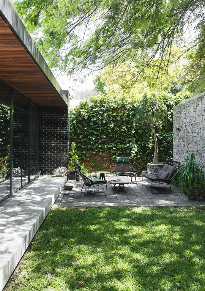 Low garden furniture works well in the small but perfectly formed outdoor space. Kettal 'Maia' outdoor sofa and chairs and 'Vieques' coffee table, all Mobilia. Porfido split stone pavers, Attica. Steel doors custom made by Steel Design.