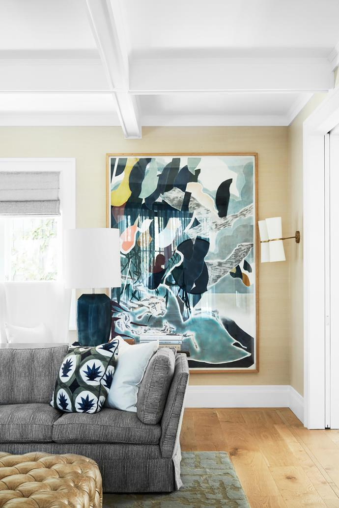 Table from Formations. In the family room, an artwork by Nathan Hawkes provides a colourful backdrop to custom sofas in a Kelly Wearstler fabric with cushions in Hermès fabric. Wall sconce from Visual Comfort. Custom leather ottoman. Robyn Cosgrove rug.