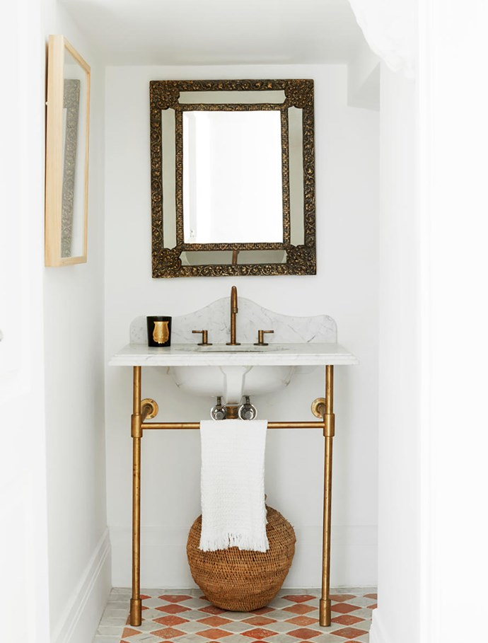 The powder room has tumbled marble tiles from Aria Stone Gallery. Pedestal and tap from The English Tapware Company with stone top by Harmony Stone Gallery. Mirror from The Vault Sydney.