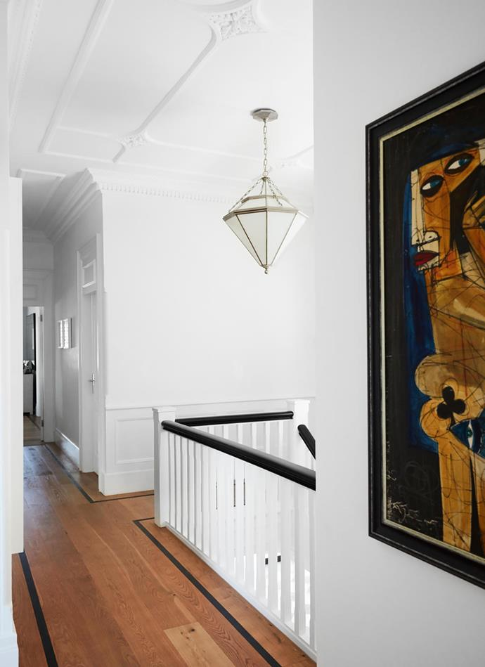 Upstairs, a Ralph Lauren lightfitting from Laura Kincade hangs over the staircase. Framed artwork sourced in Cuba.