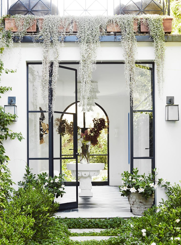 The entrance with custom steel doors, tumbled marble tiles from Aria Stone Gallery, a custom scalloped table from Den Holm and a Murano glass chandelier from New York. Pot from Garden Life. Visual Comfort 'Ojai' sconces. Limestone pavers from Eco Outdoor.