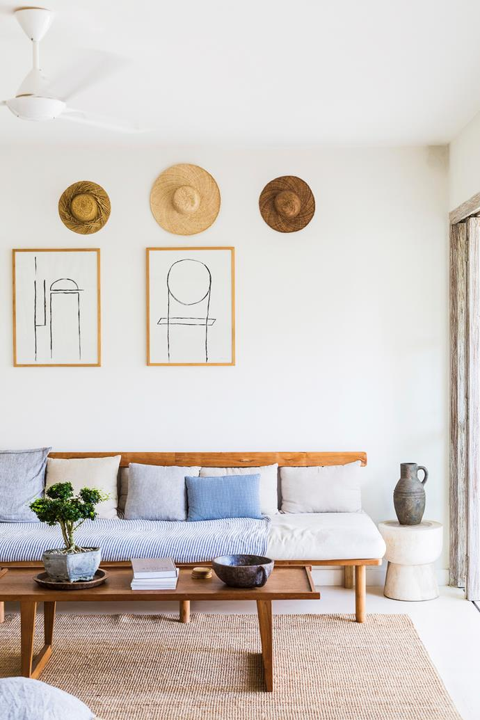 Straw hats decorate the walls of the living room, alongside artworks by homeowner Lena.