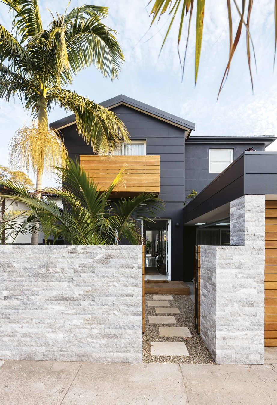 "The facade of this [tropical resort-style home](https://www.homestolove.com.au/tropical-resort-style-home-18497|target=""_blank"") is painted in bold 'Black Caviar' by Dulux, contrasting with the timber accents and 'Dogal' marble cladding from Surface Gallery on the front fence."