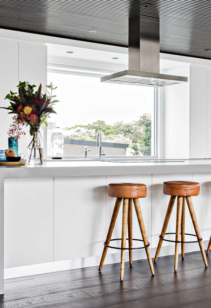 """Pete and Nic wanted a really soft, neutral, calming and relaxed space, with pops of warm neutrals, earthy tones, tan leather, timber and different blues,"" says stylist Fiona Michelon. The tan leather and timber stools in the kitchen add warmth to the [concrete benchtop](https://www.homestolove.com.au/kitchen-benchtop-guide-19237