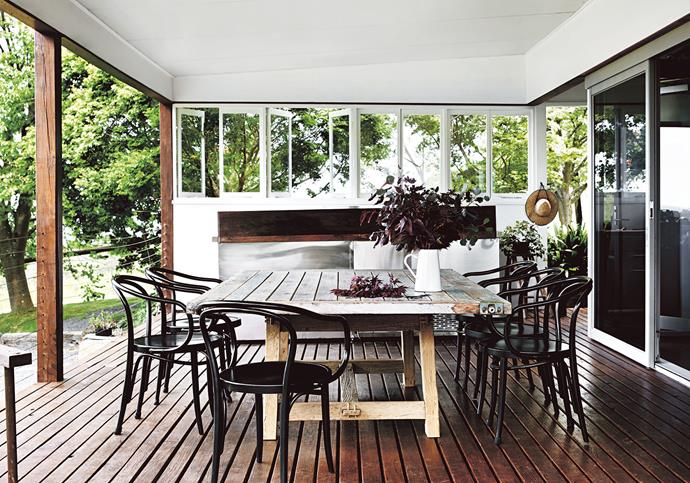 The outdoor deck and kitchen area features Thonet 'No. B9 Le Corbusier' armchairs and a table made by Don, using a recycled timber security  door for the top.
