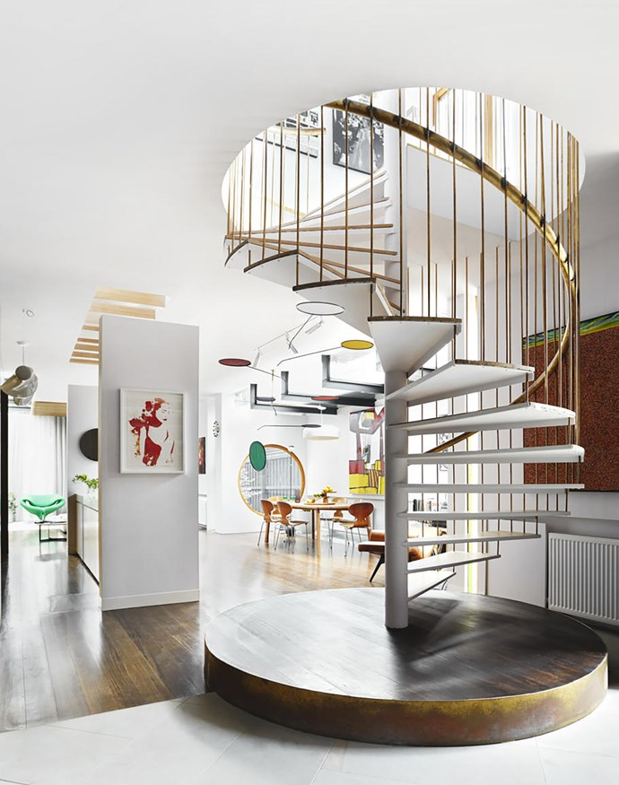 The extension's living area features a spiral staircase on a plinth, with brass handrail and rod cage. From here, the flooring transitions from limestone to solid Tasmanian oak stained with Feast Watson Black Japan. Hotchkiss 'Lumen' mobile bought from New York's Guggenheim Museum. Artworks by Vincent Fantauzzo (portrait, left) and Jerson Samson (behind staircase).