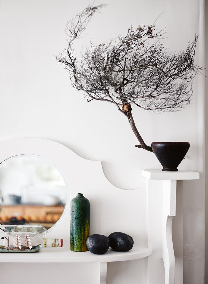 A branch found on a beach completes an arrangement of ceramic rocks and more op shop finds; behind the bed.