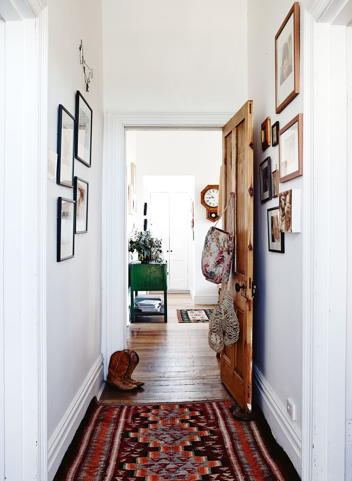 "Gallery walls of family photographs line the hallway [cottage home](https://www.homestolove.com.au/eclectic-tasmanian-cottage-13797|target=""_blank"") of jewellery maker Carmen Blyth. Just visible beyond the entrance hallway is an antique clock restored by her father. ""He spent more than 20 years of his retirement doing them,"" says Carmen."
