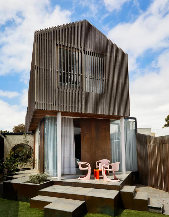 Staggered limestone tiles with brass face panels resemble an intricate puzzle, creating a unique outdoor spot. Casala '2007/2008' chairs. Upper storey clad in Cambia ash battens.