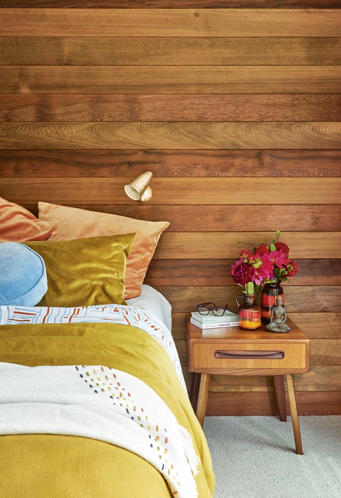 "A natural cedar panelled feature wall in the master bedroom draws the eye in, making it a cosy space for relaxation. The wall-mounted light from eBay not only frees up space on the bedside, it also highlights the texture and warm tones of the timber wall and plush bedding. The velvet quilt set from Kip & Co complements the tones of the vases, as well as the retro lines of the vintage G Plan bedside table Sarah found on eBay. Flat sheet, quilt cover and round cushion, all [Kip & Co](https://kipandco.com.au/|target=""_blank""