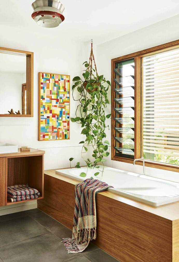 "The hard lines of the bathroom joinery, designed by Sarah and constructed by Geoff Rodgers Cabinets, are softened with the free form of the impressive hanging philodendron. Plants are important to the green-thumbed family. ""I've always grown up with plants and flowers,"" says Sarah. ""The trick with indoor plants is to not over-water!"" The vibrant tones in the artwork by Georgia Gray are held in a frame that matches the blackbutt vanity and bath surround. Bath sheets, [Sage and Clare](https://sageandclare.com/