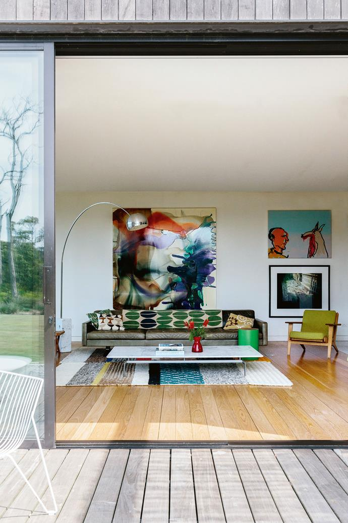 """The large artwork in the lounge room is by Dale Frank, while the piece on the top right is by Adam Cullen. """"The building and interior design was more James's labour of love than mine. I'm more outside. But I'm [happy with colour](https://www.homestolove.com.au/in-living-colour-3220