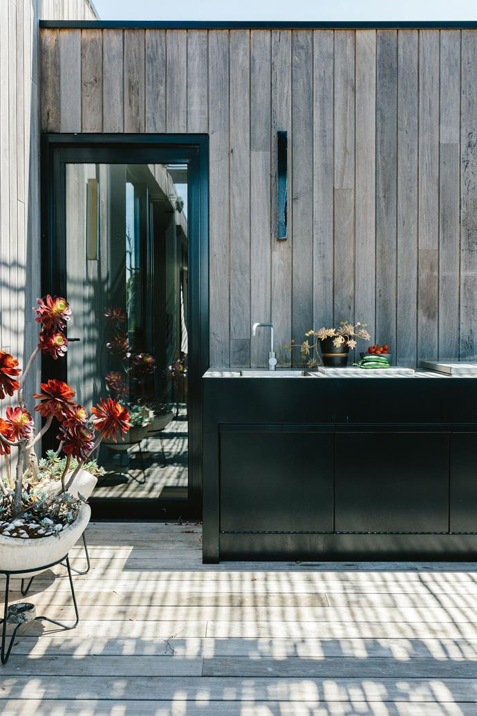 """The end of the deck features an [outdoor kitchen](https://www.homestolove.com.au/outdoor-kitchen-design-tips-6264