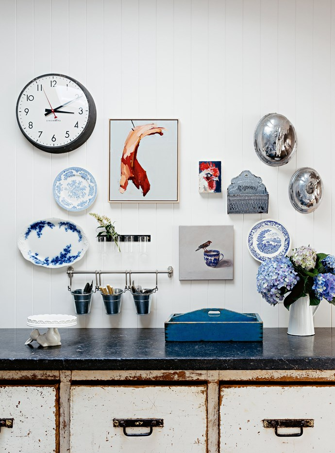 A collection of vintage china hangs above a rustic sideboard.