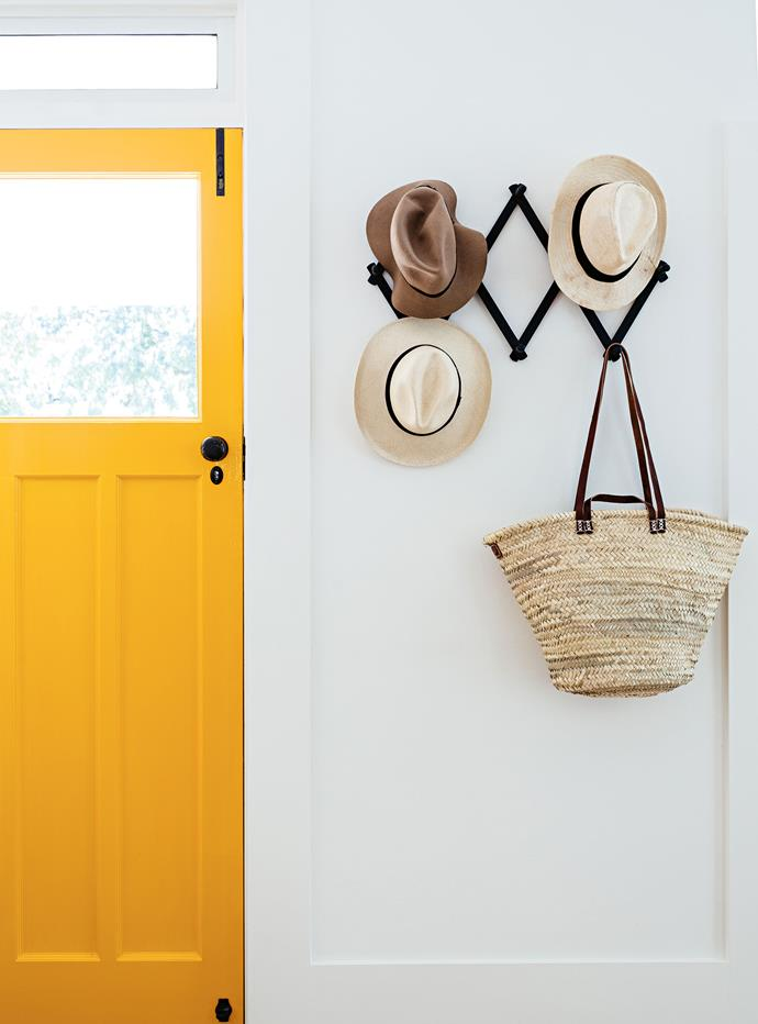 "Hats are stored by the [statement front door](https://www.homestolove.com.au/front-door-colour-ideas-19810|target=""_blank"") which was painted a sunny shade of yellow, Dulux Gold Rush."