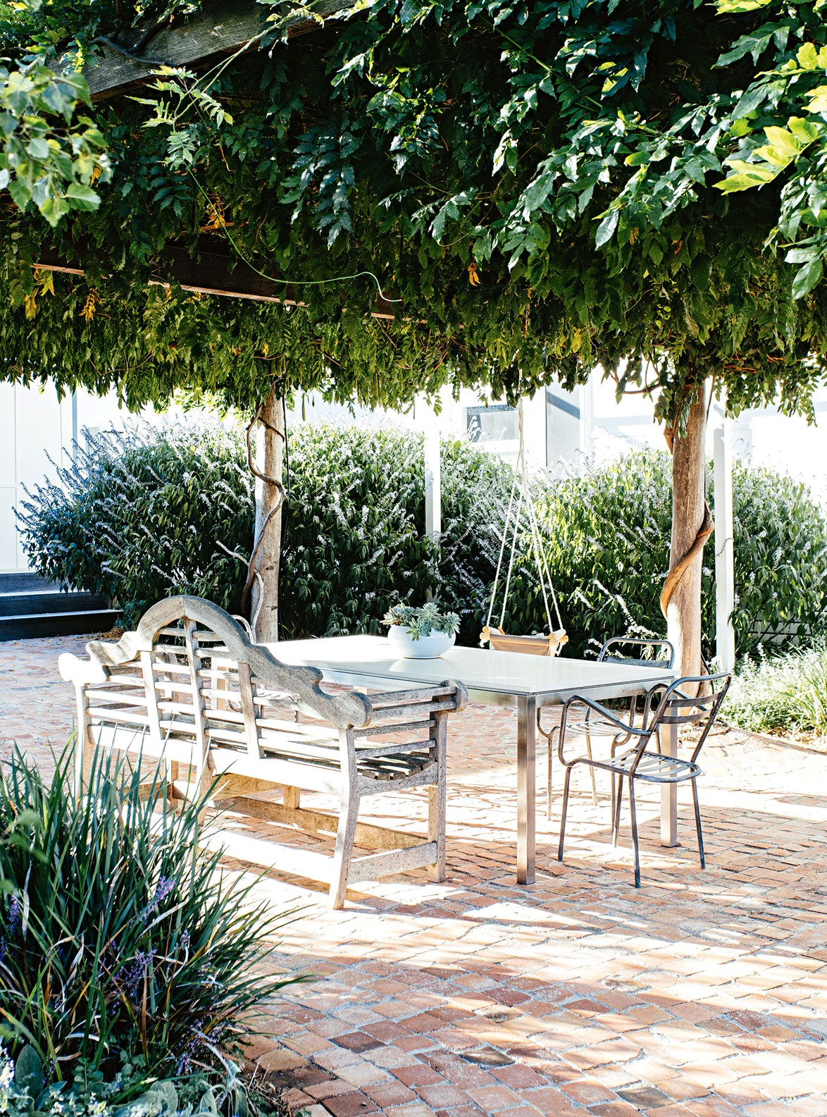 "A brick-paved outdoor patio, shaded by an arbour covered in climbing wisteria, provides the perfect place for the owners of this [modern shaker country home](https://www.homestolove.com.au/modern-shaker-country-home-13758|target=""_blank"") overlooking Mudgee wineries to entertain or unwind with a glass of vino from their own cellar door."