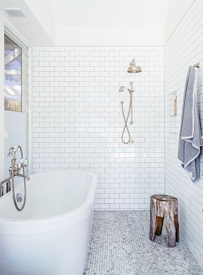 "To give the ensuite [bathroom a hotel ambiance](https://www.homestolove.com.au/bathroom-trends-inspired-by-boutique-hotels-19168|target=""_blank""), Hannah chose Carrara marble penny rounds for the floor from Academy Tiles. On the walls are subway tiles, with grey grout."