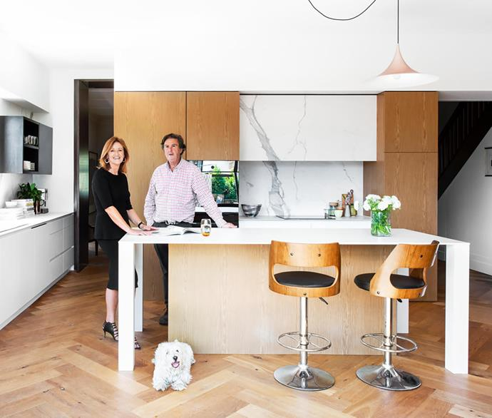 """""""The existing floor was replaced for consistency,"""" says architect Jane Riddell who, in conjunction with owner Hugh (both pictured, with West Highland terrier Fergus), chose Grande oak floorboards in Chamoisee from Tongue N Groove. Other materials include Dekton in Zenith (island bench), Statuario marble (splashback) and Eveneer timber veneer in Almond (cabinetry throughout). V-Zug induction cooktop and wall oven. Gaggia coffee machine."""
