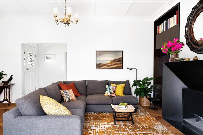 Once marooned at the front of the house, this room now has a connecting door to the kitchen. Hugo modular sofa (upholstered with Barclay fabric in Coal) and rug, both Boyd Blue. Landscape painting by Wim Kortland. Designer buys: Lanyard bamboo and rattan mirrors, $5170 each, Boyd Blue.