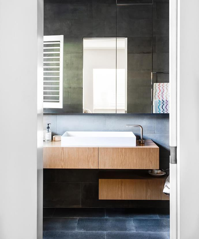 Bluestone tiles perfectly complement the light wood veneer cabinets. Large expanses of mirror from waist height make the space feel much bigger. Missoni towels, Safari Living.