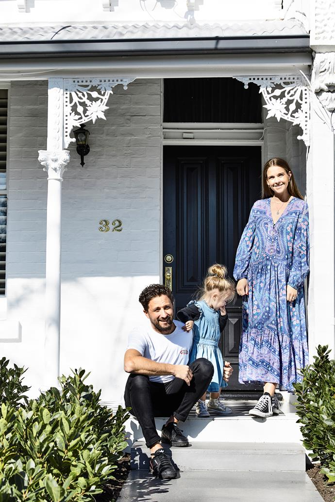 """""""We love how our house looks relatively unassuming and traditional from the street, until you step inside,"""" says Travis, who's pictured here on the porch with Catherine and Hazel."""