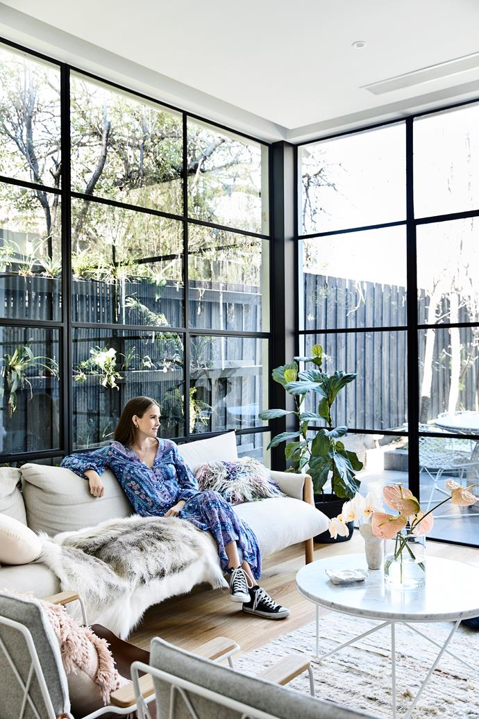 The floor-to-ceiling windows, made by Steel Window Design, are one of the couple's fave new features. Catherine relaxes on a Wilfred sofa from Jardan.
