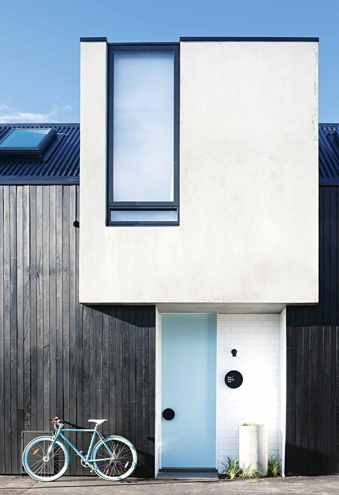 """Planning was interesting because there's a heritage overlay on the whole precinct. The old house was very run-down – it had [fake brick cladding](https://www.homestolove.com.au/home-exterior-materials-14909 target=""""_blank"""") and all the windows had been changed, so the council was very happy to see it go. Council was also very interested in what was going in its place. The new build had to be respectful of character, height, form and such.<br><br>Take a tour of the townhouse next to George and Lisa's. The two homes are very similar but have a few points of difference. **Exterior** Both facades feature [natural cement render](https://www.homestolove.com.au/home-exterior-materials-14909 target=""""_blank""""), silvertop ash timber lining boards stained with black Woca exterior oil and a [front door](https://www.homestolove.com.au/front-door-colour-ideas-19810 target=""""_blank"""") painted in [Dulux](https://www.dulux.com.au/ target=""""_blank"""" rel=""""nofollow"""") Aqua Frost."""