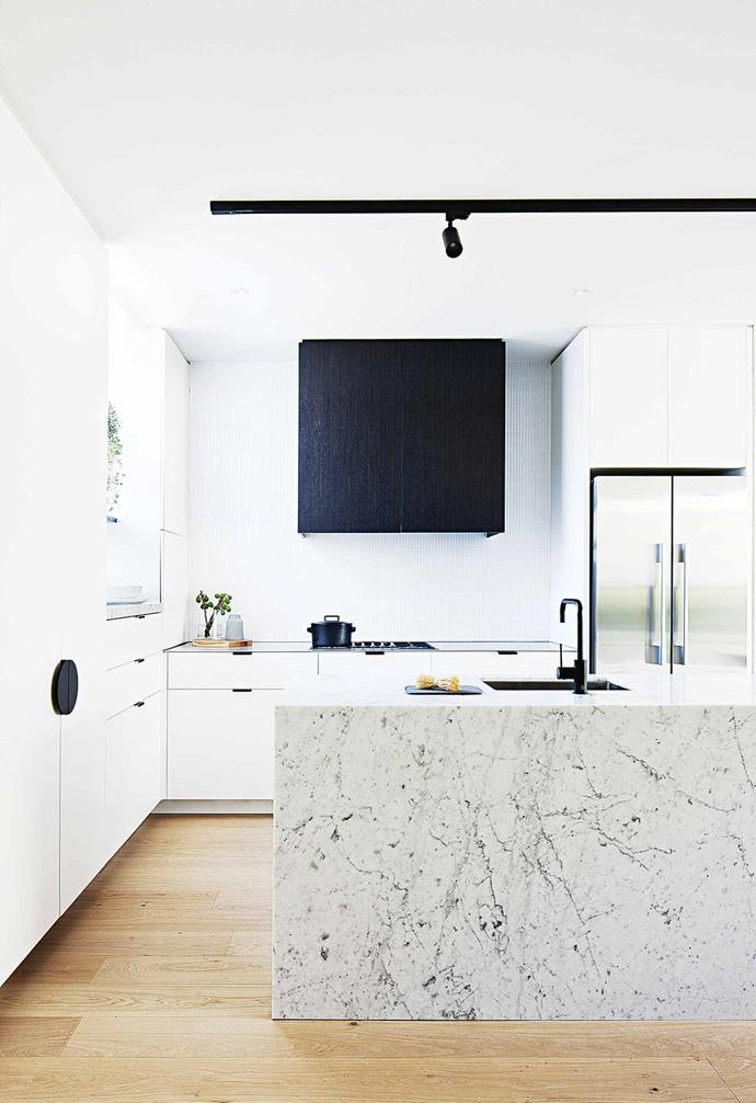 """**What was your overall plan for the interior?** To keep it clean and simple. We both find that the house has a very calming palette with its natural tones – timber, concrete and natural materials in the rugs. We wanted to rely on texture in the materials rather than overload it with joinery or elaborate detail.<br><br>**Kitchen** Touches of black are a nod to the veined marble [island bench](https://www.homestolove.com.au/kitchen-inspiration-13-of-the-best-island-benches-17943 target=""""_blank"""")."""