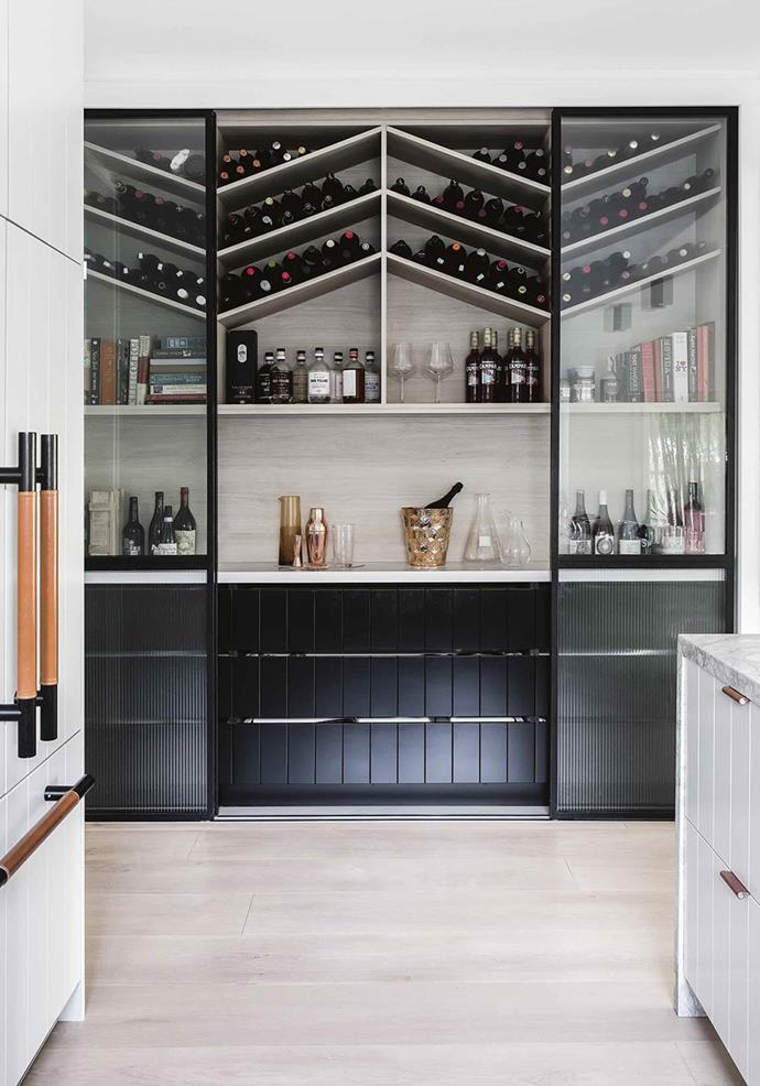 This postwar 1940s weatherboard beach house on Sydney's Northern Beaches received a minimalist, family-friendly update. Its major drawer card? Its luxe dolomite marble kitchen and dedicate bar.  <br><br> To make the drinks area a feature, the owners chose open-shelving to showcase their wine collection. As a bonus, storing the bottles horizontally and at the highest point helps keep corked wine in particular, in top condition. Statement glass doors and curated styling make this space one guests will always remember. *Photo: Maree Homer / bauersyndication.com.au*