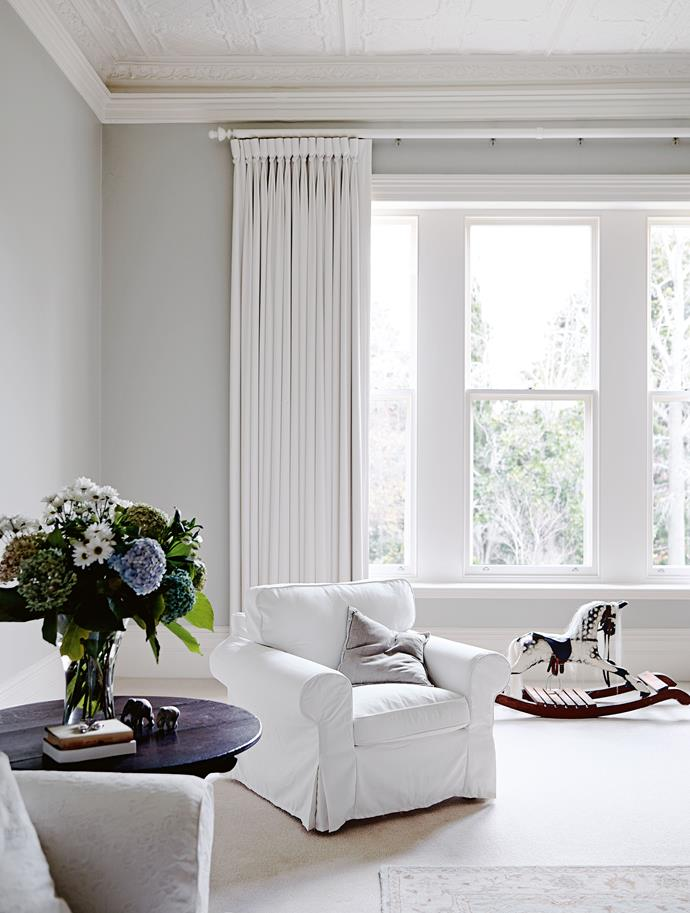"Soft grey and off-white in the sitting room. Jane bought Scruffy the rocking horse when the boys were babies. The white lounge suite has moved with them to all their homes. During the [first year of renovations](https://www.homestolove.com.au/renovation-timeline-how-to-plan-your-reno-18861|target=""_blank""), the family ""camped"" in the house with few comforts — ""We huddled in one room in front of a fire in winter,"" Kym says. ""When you breathed there was mist in the air... We did everything to the house you could think of. It needed reroofing, replastering, wiring, replacing windows — and the verandah posts had to be redone."""