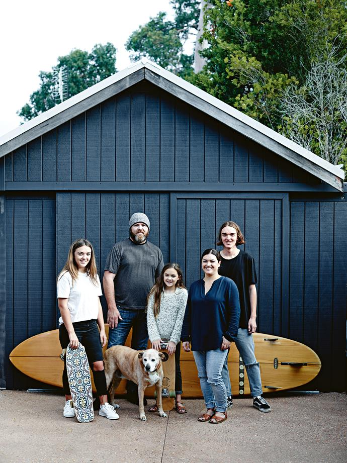 Ella, Craig, Issey the ridgeback–cross, Aniah, Rachel and Jack outside the shed that Rachel hopes will become her studio one day. Rachel's paddleboard leans against the shed.
